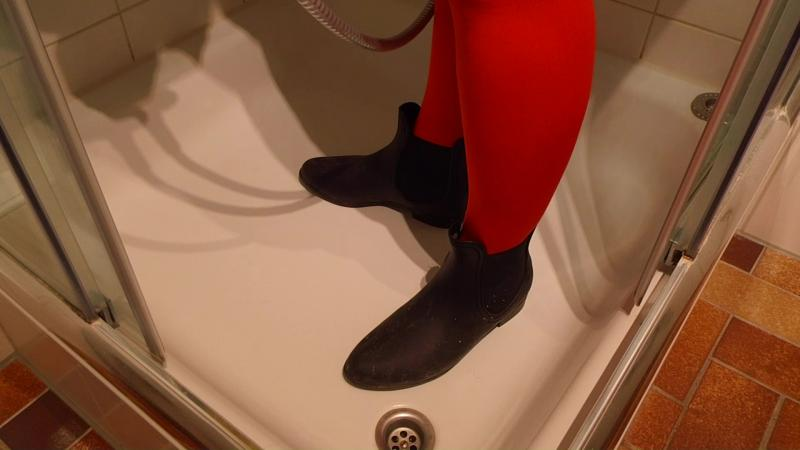 Jana slices her black chelsea rubber ankle boots in the shower on her feet