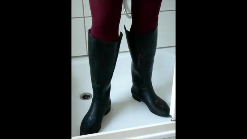 Jana write on, fill and destroy her black rubber riding boots in shower