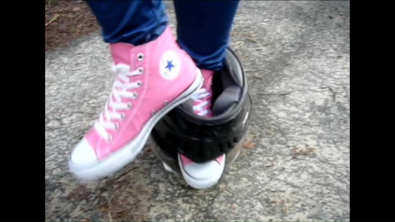 Jana tramples on a motorcycle helmet with her pink chucks